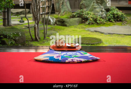 A Japanese teaset of traditional green tea and wagashi (Japanese sweet confectionery) served by a beautiful Japanese - Stock Photo
