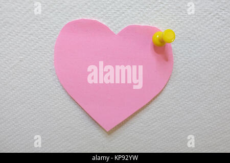 Note paper in heart shape with yellow pin posted on white cork board background - Stock Photo