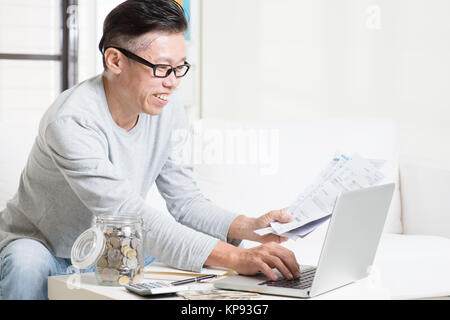 Paying bills online using computer - Stock Photo