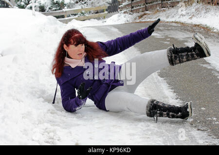 danger of accidents in winter - a woman has slipped on a snowy road - Stock Photo