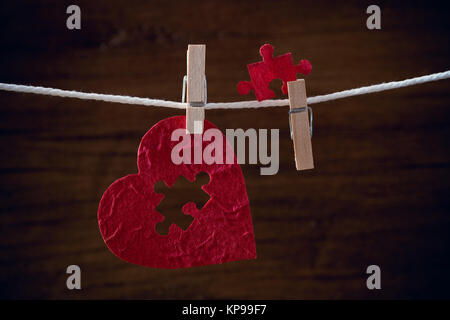 heart love jigsaw on cloth rope - Stock Photo
