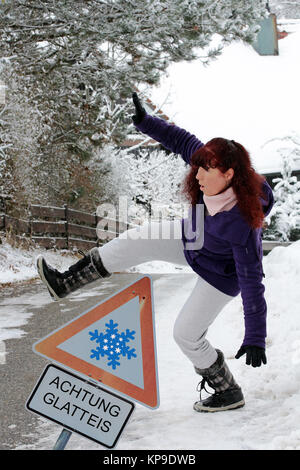 warning danger of accidents in winter - a woman slips out on a snowy road - Stock Photo