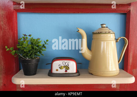 Retro kitchenware and plant pot on wooden shelf, blue background with red frame - Stock Photo
