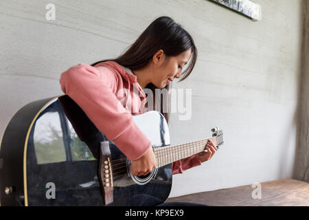 Asian Woman play with guitar at home - Stock Photo