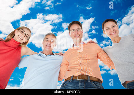 Two happy couples looking down - Stock Photo
