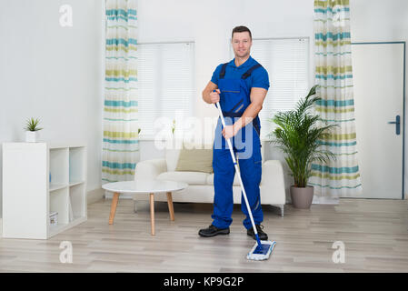 Smiling Worker Cleaning Floor With Mop At Home - Stock Photo