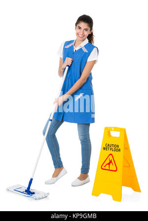 Happy Janitor Mopping By Caution Wet Floor Sign - Stock Photo