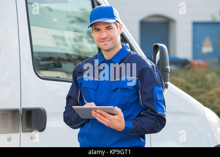 Delivery Man Smiling Using Digital Tablet By Truck - Stock Photo