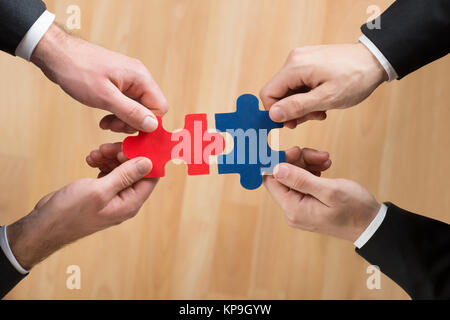 Cropped Image Of Businessmen Assembling Jigsaw Puzzle - Stock Photo