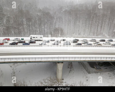 Cars on a highway bridge during a heavy snowfall in winter - Stock Photo