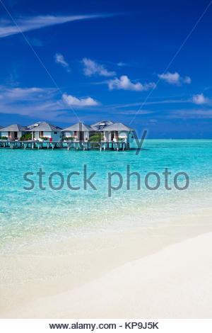 Water villas in the ocean and white sandy beach - Stock Photo