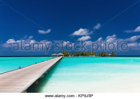 Wooden jetty to a tropical island over lagoon in Maldives - Stock Photo