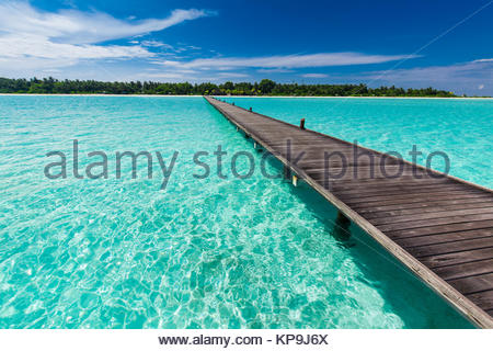 Wooden long jetty over lagoon in Maldives with amazing water - Stock Photo