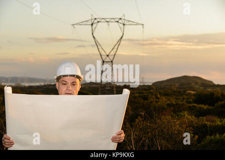Electrical Engineer, Controls Power Line and wind turbines at sunset outdoors in the countryside - Stock Photo