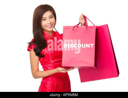Chinese Woman hold with red paper bag and showing a word discount - Stock Photo