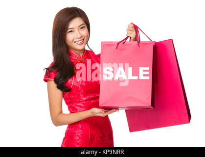 Chinese Woman hold with red paper bag and showing a word sale - Stock Photo