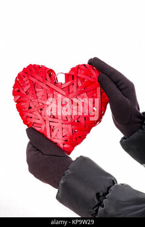 Hands With Gloves Hold Red Wicker Heart. - Stock Photo