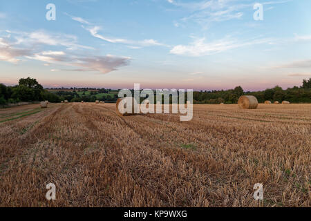 Late Summer sunset over field with hay bales - Stock Photo