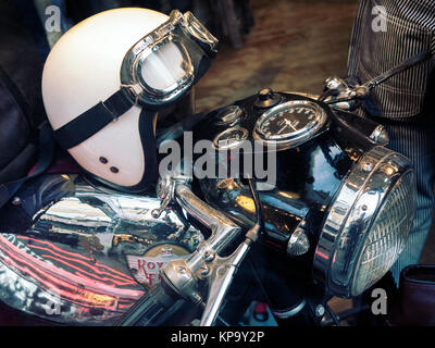 Royal Enfield motorcycle with classic crash helmet on the petrol tank - Stock Photo