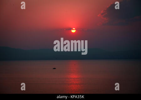 Lonely yacht in the sea on the background of a beautiful red sunset on a summer evening. - Stock Photo
