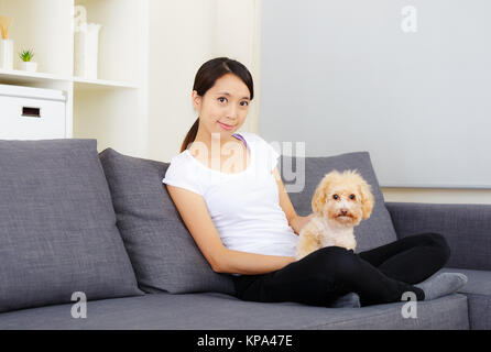 Asia woman and poodle at home - Stock Photo