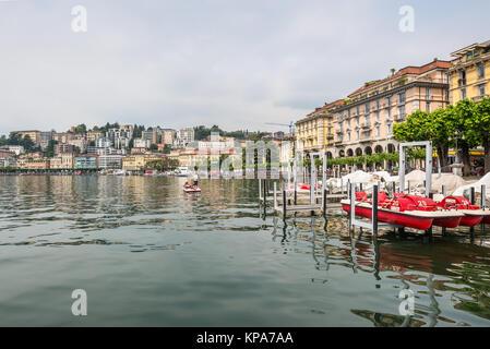 Lugano, Switzerland - May 28, 2016: View of embankment of Lugano Lake. Lake Lugano (Lago di Lugano) is nestled between - Stock Photo