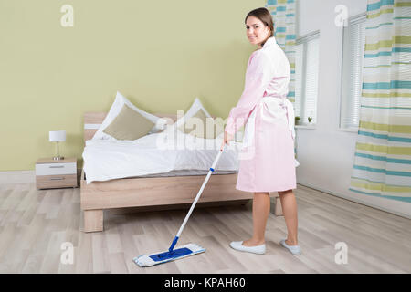 Female Housekeeper Cleaning Floor With Mop - Stock Photo