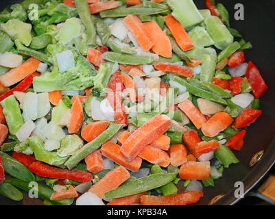 An assortment of raw frozen vegetables in a non stick skillet ready for cooking. .Frozen  carrots, peppers, beans, - Stock Photo