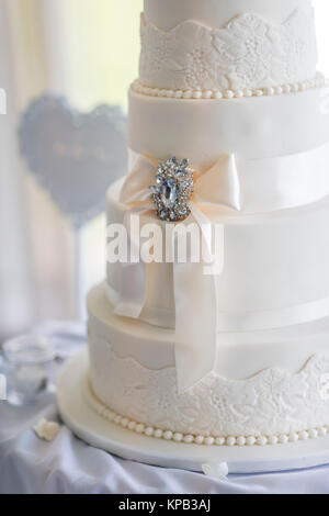 Wedding cake at a reception decortaed with flowers - Stock Photo