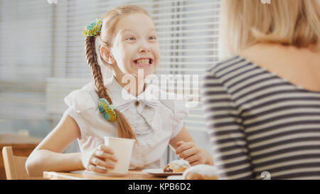 Daughter and mother are sitting in a cafe, eating sweetsand talking emotionally - Stock Photo