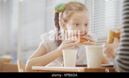 Girl with pigtail is eating sweets in the cafe - Stock Photo