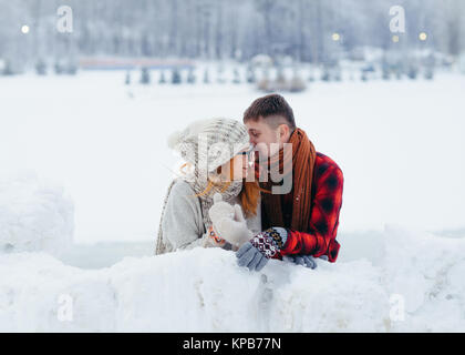 The handsome man is whispering something funny in the ear of his laughing girlfriend. Winter village location. - Stock Photo