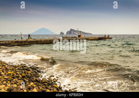 Rocky coast boarding pier of the island of panarea and in the background the volcano Stromboli and two rocks emerging - Stock Photo