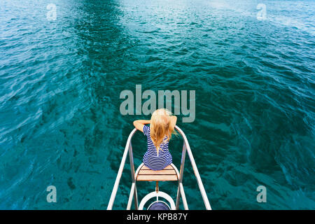 Joyful child portrait. Happy little baby girl on board of sailing yacht have fun discovering islands in tropical - Stock Photo