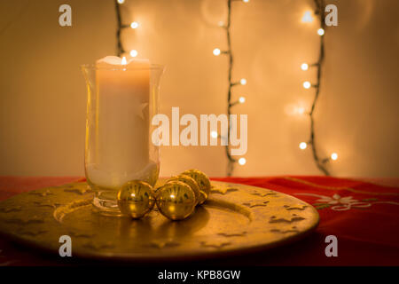 Christmas candles burning and golden balls, tree decorations. Dish with stars pattern. Red decorated fabric on the - Stock Photo