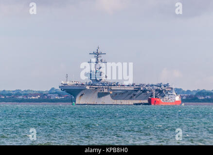 American aircraft carrier, USS George HW Bush visiting Portsmouth, anchored in The Solent at Stokes Bay, near Gosport - Stock Photo
