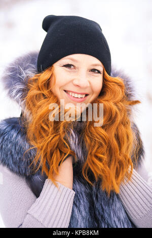 Portrait of beautiful young girl dressed in fur coat at winter background. Beauty woman having fun outside on winter - Stock Photo