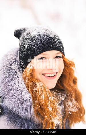 Portrait of beautiful young girl dressed in fur coat and black hat at winter snowy trees background. Beauty woman - Stock Photo