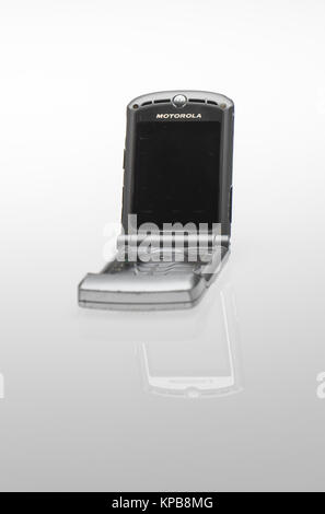 An old style Motorola flip up mobile phone on a white background. - Stock Photo