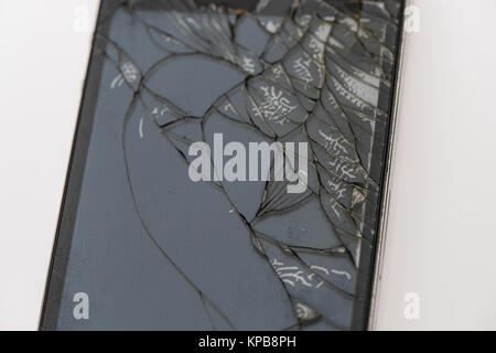 A badly cracked second generation iPhone on a white background - Stock Photo