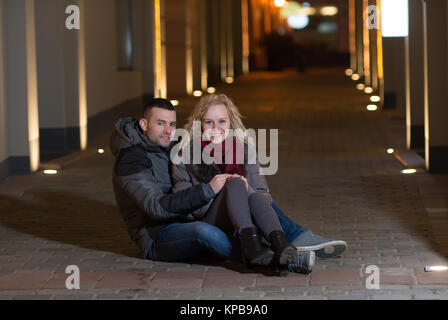 Romantic couple sitting on the street,is beautiful Christmas night - Stock Photo