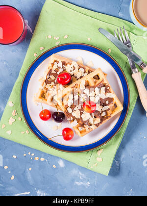 Sweet treat belgian waffles with chocolate almond shreds and cherries on blue textured background - Stock Photo