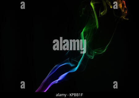 Flowing rainbow smoke against the black background - Stock Photo