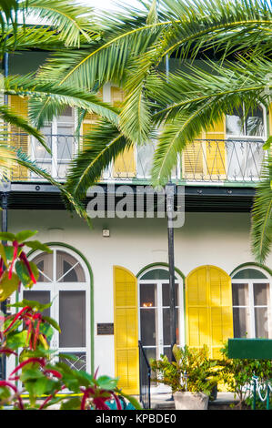 Ernest Hemingway Home & Museum yellow shutters, balcony and palm trees, Key West, Florida - Stock Photo