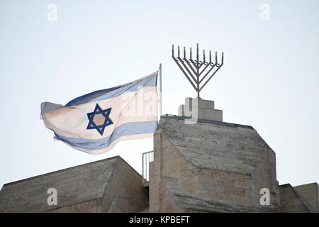 Very high resolution late afternoon view of an Israeli flag flying next to a menorah near the top of a building - Stock Photo