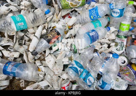 Plastic bottles, aluminium cans and other rubbish in pile on ground - Stock Photo