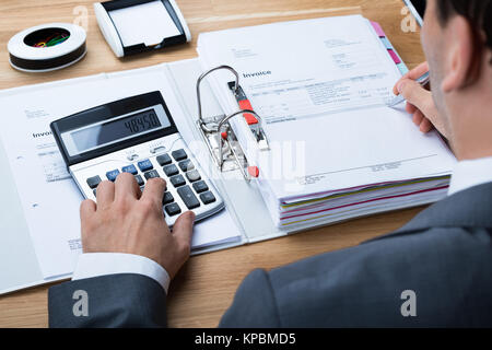 Businessman Calculating Invoice At Office Desk - Stock Photo