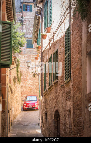 Characteristic and pretty side street in Tuscany, with a red Fiat 500, Cinquecento parked in the distance. - Stock Photo
