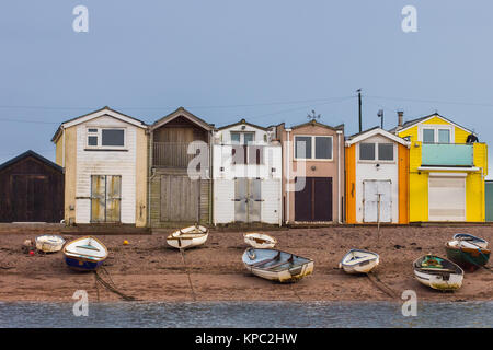 Boats scattered on the beach of the River Teign in front of colorful boat houses - Stock Photo