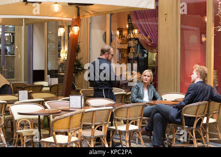 Man and Woman sitting in a Paris Cafe - Stock Photo